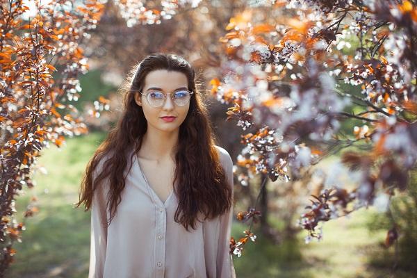 Ukrainian woman outdoors near spring blossom tree in the park