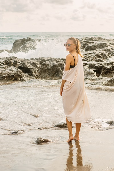 Pretty Ukrainian woman near danger rocks on ocean shore staying barefoot