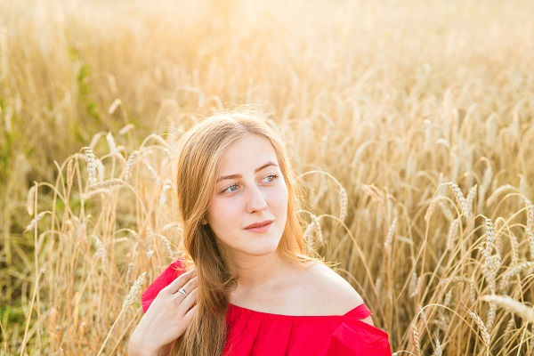 Beautiful Ukrainian girl in the wheat field at sunset watching sideward