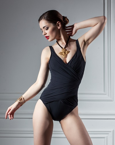 Sexy Ukrainian woman posing in a black swimsuit with her hands touching back in interior