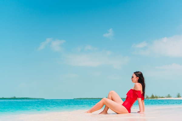 Young fashionable Ukrainian girl in a red swimsuit lying and sunbathing on the beach