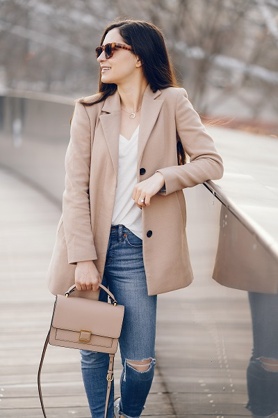 Fashionable Ukrainian girl walking alone wearing a nice coat in a spring park