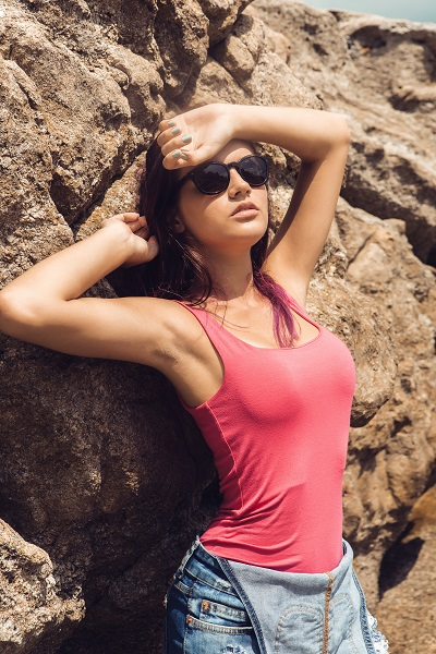 Sexy young Ukrainian girl wearing a pink T-shirt and sunglasses near bag rocks