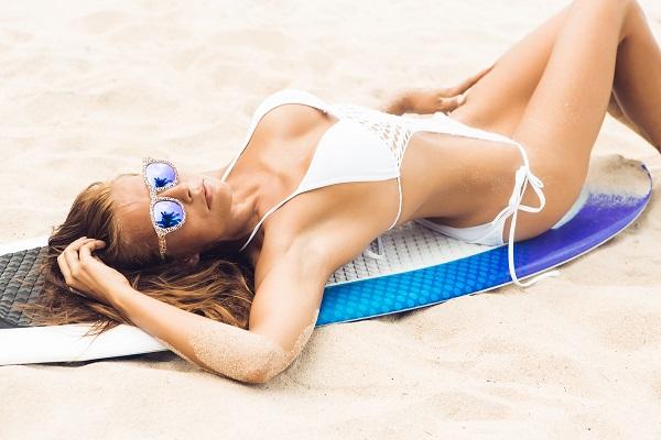 Sexy surfer Ukrainian girl lying and sunbathing on the sea ocean beach