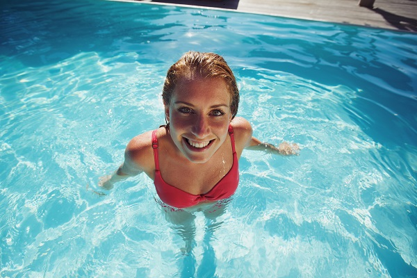 Pretty young Ukrainian woman relaxing and smiling at the camera in a swimming pool