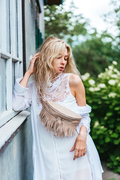 Ukrainian blonde woman posing with a stylish bag with her eyes closed wearing a white handmade dress