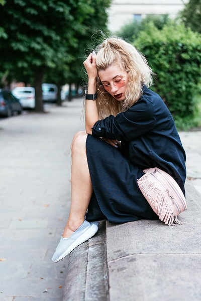 Serious Ukrainian blonde woman sitting on the street with a fashionable bag all alone