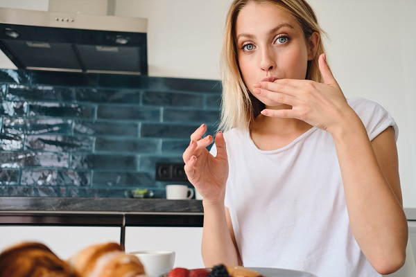 Pretty blond Ukrainian woman dreamily looking in the camera licking her fingers having breakfast at home