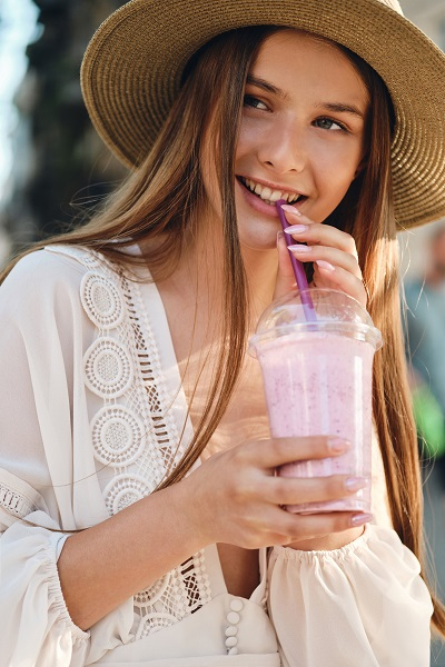 Attractive smiling Ukrainian girl in a white dress and hat drinking her smoothie on a cozy street