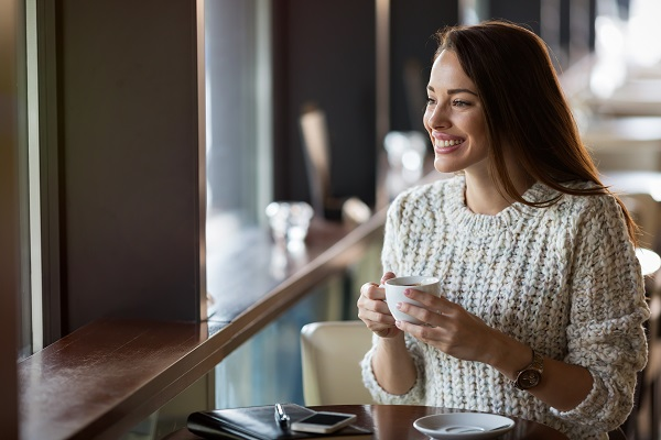 Beautiful smiling Ukrainian woman drinking coffee in the restaurant alone