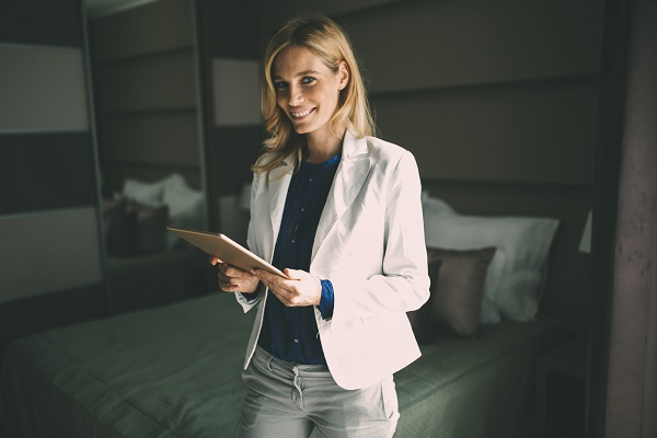Elegant smiling Ukrainian businesswoman staying in the hotel wearing jeans and a white shirt